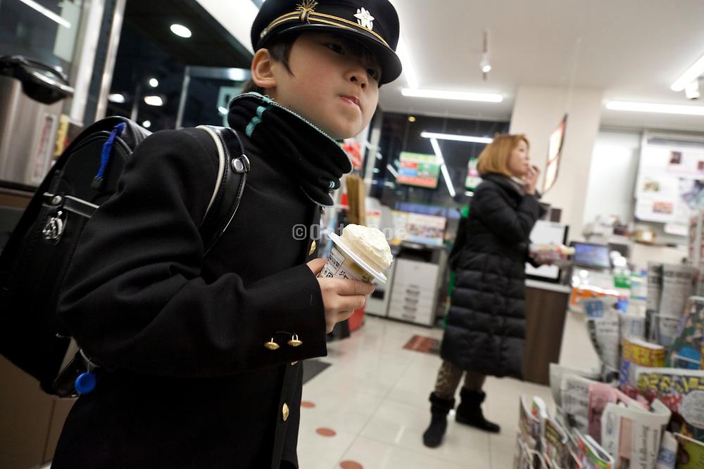 little uniformed school boy holding an ice cream inside a convenient store Japan Tokyo