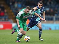 Leatherhead's Niall McManus (left) is tugged back by Wycombe Wanderers' Matt Bloomfield (right) during the Emirates FA Cup, second round match at Adams Park, Wycombe.
