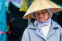 Disillusioned: In the morning market an elderly woman wears a profoundly disillusioned  expression, born of her lifes' experience, Hue Vietnam.