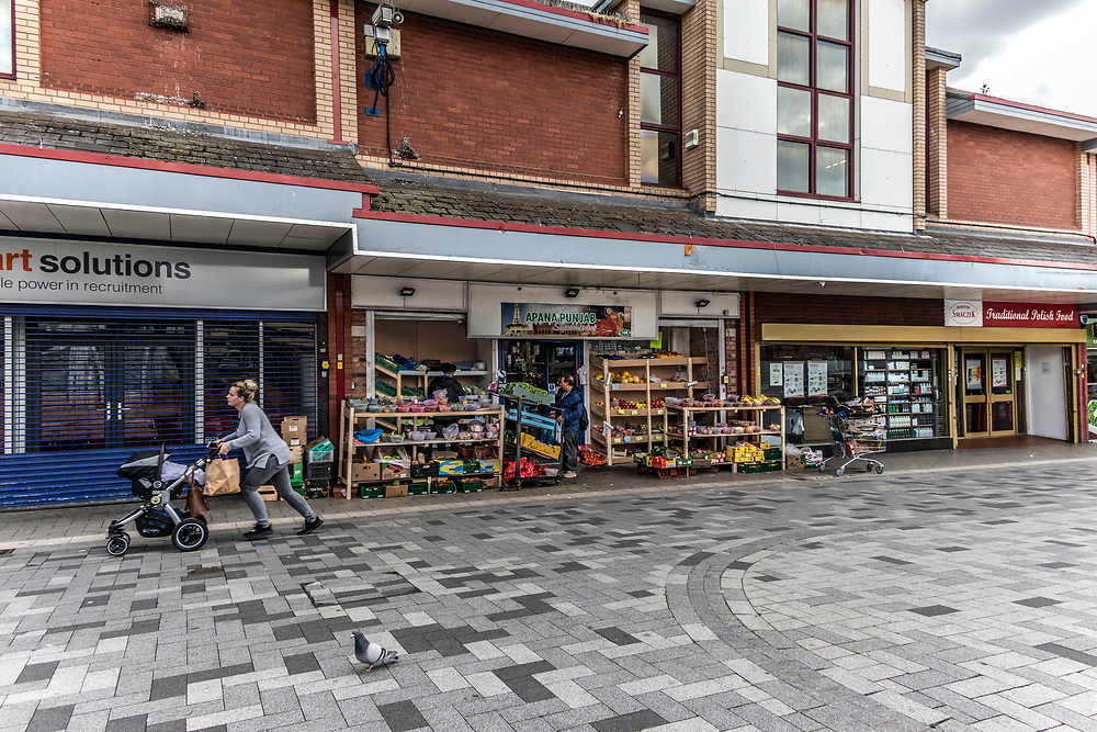 Part of the high street, West Bromwich, West Midlands, UK.<br />Young mother pushing child in a buggy, runs past a local Indian  supermarket.