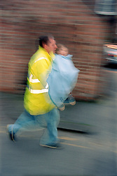 Young child wrapped in blanket being carried by worker from emergency services,