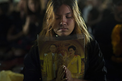 October 22, 2016 - Bangkok, Thailand - Thai mourners wearing black hold portraits of late Thai King Bhumibol Adulyadej during the royal religious praying rites for the king outside Grand Palace in Bangkok, Thailand on October 22, 2016. (Credit Image: © Anusak Laowilas/NurPhoto via ZUMA Press)
