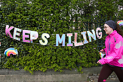 """© Licensed to London News Pictures. 01/04/2020. London, UK. A woman walks past a 'KEEP SMILING"""" hand painted sign displayed outside a school in north London as coronavirus lockdown continues. Rainbows are used as a symbol of peace and hope. Photo credit: Dinendra Haria/LNP"""