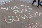 People pass a climate activism message written in chalk on the floor, urging people to go vegan to save the planet from the consequences of global warming and climate change on 8th August, 2021 in Leeds, United Kingdom. The Intergovernmental Panel on Climate Change IPCC has released an alarming report on the state of Earths climate, highlighting unprecedented changes that may be irreversible.