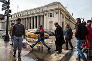 A black man steps over a large puddle opposite the United States Post Office, Eighth Avenue, New York City, New York, Unites States of America.  The puddle was caused by melting snow from the record breaking snowstorm January 2016.  Other pedestrians wait to walk past the water and there is traffic on the road behind.