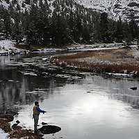 Angler in river during winter.