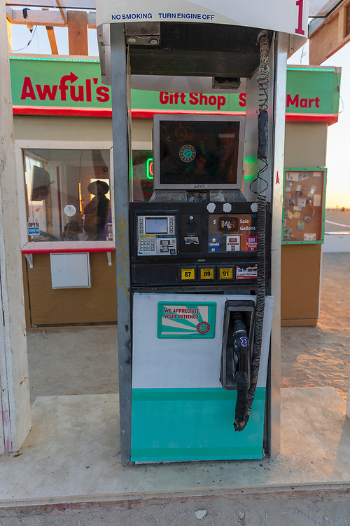 """Awful's Gas & Snack<br /> by: Matthew Gerring & Crank Factory<br /> from: San Francisco, CA<br /> year: 2019<br /> <br /> Awful's Gas & Snack: Your Gateway to the Big Wild! See one of the few remaining gasoline stations, painstakingly preserved since the mid-21st century. Travel back to a time when hardy men roamed the """"open road"""" seeking fortune & freedom. Wilderness passes & provisions available. NO GAS AVAILABLE FOR PURCHASE, PLEASE DON'T ASK.<br /> <br /> URL: http://awfulsgas.com<br /> Contact: awfuls@awfulsgas.com<br /> <br /> https://burningman.org/event/brc/2019-art-installations/?yyyy=&artType=H#a2I0V000001AVwVUAW"""