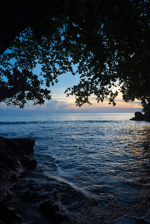 The sun sets on a small beach on the volcanic island of Karkar, located in Madang Province, Papua New Guinea.