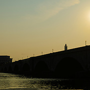 The sun rises above Memorial Bridge, seen from the Arlington, VA, side, as it spans the Potomac. The Lincoln Memorial is silhouetted on the far side at left of frame.