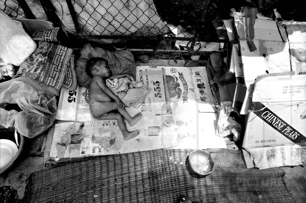 A homeless child is sleeping outside without clothes while flies are surrounding him, Phnom Penh, cambodia, Asia.