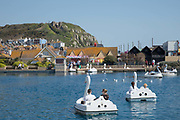 People using swan-shaped pedalos at a seaside boating lake on the 20th April 2019 in Hastings in the United Kingdom. Hastings is a town on England's southeast coast, its known for the 1066 Battle of Hastings.