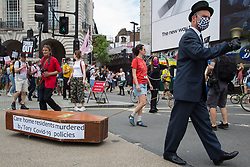A man dressed as an undertaker pulls a coffin representing care home residents who have died during the Covid-19 pandemic on the United Against The Tories national demonstration organised by the People's Assembly Against Austerity in protest against the policies of Prime Minister Boris Johnson's Conservative government on 26th June 2021 in London, United Kingdom. The demonstration contained blocs from organisations and groups including Palestine Solidarity Campaign, Stand Up To Racism, Stop The War Coalition, Extinction Rebellion, Kill The Bill and Black Lives Matter as well as from trade unions Unite and the CWU.