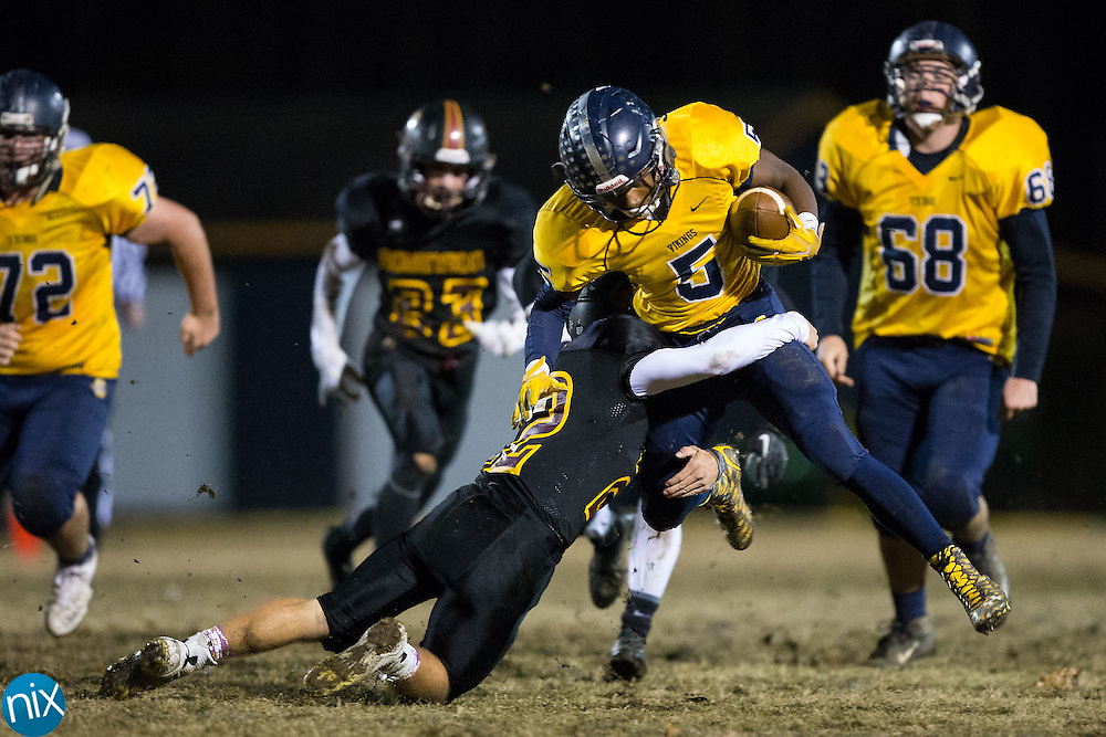 Lundon White (5) of the South Iredell Vikings is tackled by Dawson Williams (22) of the JM Robinson Bulldogs during first half action at South Iredell High School November 20, 2015, in Statesville, North Carolina.  The Vikings defeated the Bulldogs 14-13.  (Brian Westerholt/Special to the Tribune)