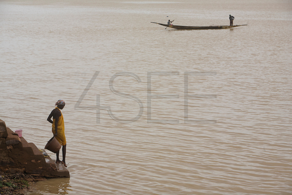 Woman collecting water from the river. At the confluence of the Niger and the Bani rivers, between Timbuktu and Ségou, Mopti is the second largest city in Mali, and the hub for commerce and tourism in this west-african landlocked country.