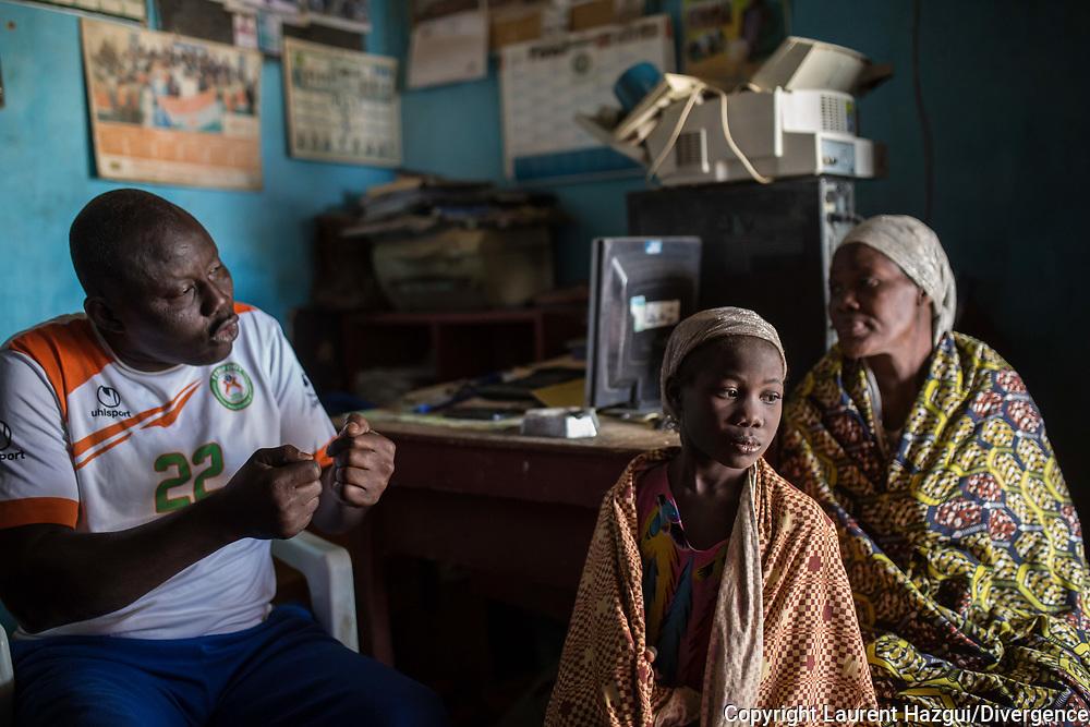 27012018. Niger. Agadez. Autogare où passent de nombreux migrants sur la route de l'Algérie et de la libye. Issa Ikilila, ancien passeur, à la tête de l'Association d'appui aux migrants et aux refoulés d'Algérie et de libye. Il accueille des migrants et les alerte sur les dangers du voyage dans le désert en Libye. Une mère de famille nigérianne en détresse vient le voir avec ses deux filles. Elle souhaite continuer la route vers la libye malgré les mises en garde d'Issa Ikilila. Elle n'a plus d'argent.