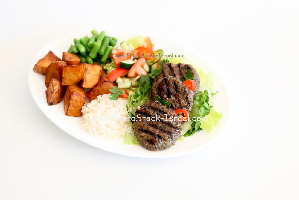 Kebab with salad, rice and potatoes