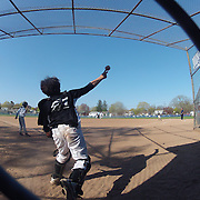 The catcher throws the ball from the back of the batting cage during the Norwalk Little League baseball competition at Broad River Fields,  Norwalk, Connecticut. USA. Photo Tim Clayton