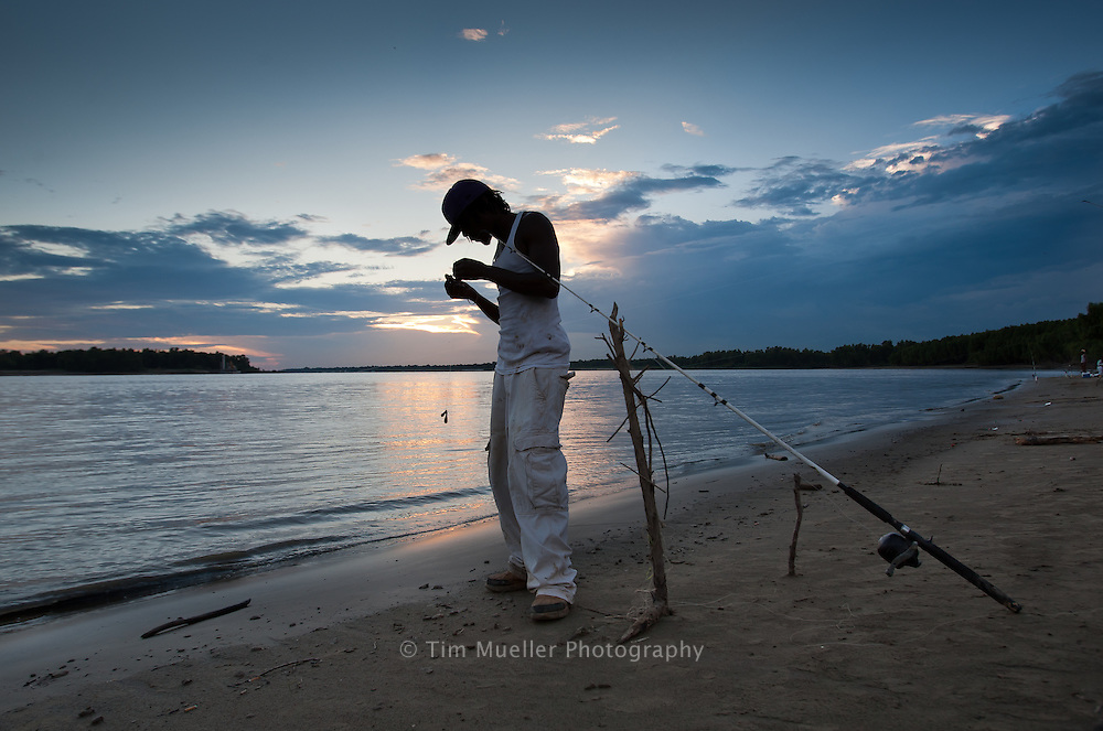 """As the sunsets on the Mississippi River, Brandon Williams, 21, prepares his gear while fishing below the Bluffs at Southern University. Williams says this is his second time fishing on the banks of the Mississippi river and he just caught a big ole Goo. """"I like to fish,"""" says Williams, """"especially when you catch a lot of fish."""""""