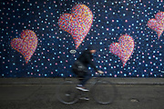 Graffiti artist Jimmy C cycles past his mural at Borough Market which serves as a personal dedication and homage to the terror attack at London Bridge on 4th April 2017 in London, United Kingdom. The heart shapes, which are a regular fixture of the artist's work are a call to respond with love not fear. While the piece is not specifically designed as a memorial to those who died on June 3rd 2017, it is already being taken into people's hearts where the attacks took place, and seems inevitable to become a focus for remembrance and commemorations in the future.