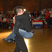Claudia Neidig, left, carries her dance partner, Kristin Marunke, both of Berlin, Germany, to the medal stand after winning the gold medal in the women's standard C division of the same-sex ballroom dancing competition during the 2007 Eurogames at the Waagnatie hangar in Antwerp, Belgium on July 14, 2007. ..Over 3,000 LGBT athletes competed in 11 sports, including same-sex dance, during the 11th annual European gay sporting event. Same-sex ballroom is a growing sports that has been happening in Europe for over two decades.