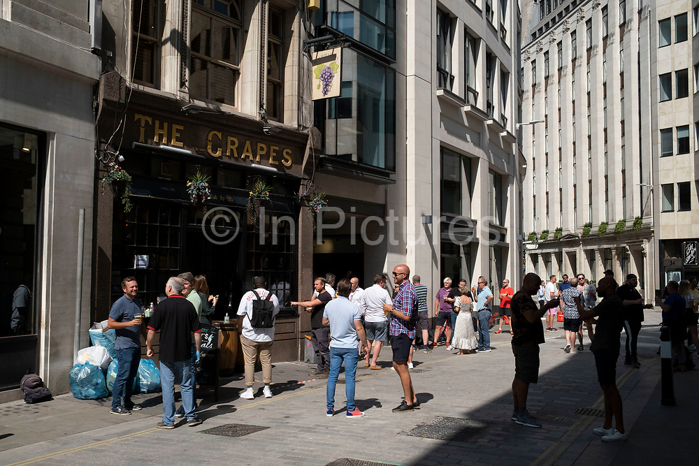 On the day that it was announced that the Coronavirus lockdown measures are set to ease even further, drinkers outside a pub in the City of London enjoy some take out drinks at The Grapes pub on 23rd June 2020 in London, England, United Kingdom. The government has relaxed its lockdown rules, and from early July is allowing spubs to reopen, as long as they have set up social distancing systems.