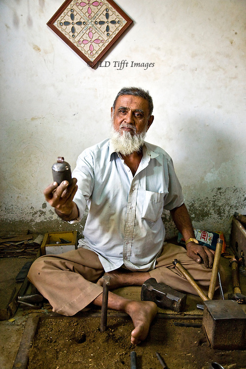 The bell maker, Nivona village, Kutch, Gujarat, proudly holds up a bell he has just made.  He is seated in his workshop, his few tools beside him.