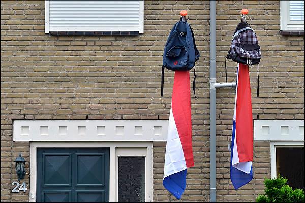 Nederland, Wijchen, 13-6-2015Vlag met boekentas is uitgehangen om te vieren dat het eindexamen is gehaald. Deze week hebben scholieren van het voortgezet onderwijs de uitslag van hun eindexamen gekregen. Bij veel geslaagden gaat traditioneel de vlag uit, met de schooltas aan het einde van de stok. Hier betreft het twee vlaggen met tassen van buurkinderen. Foto: Flip Franssen/Hollandse Hoogte