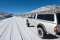 4 wheel drive truck on Snow covered high desert road, Death Valley national park, California