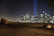 A girl is watching the ray of lights coming up from the Wall Street skyline on the September 11 anniversary, Brooklyn Heights Promenade, New York, 2010.