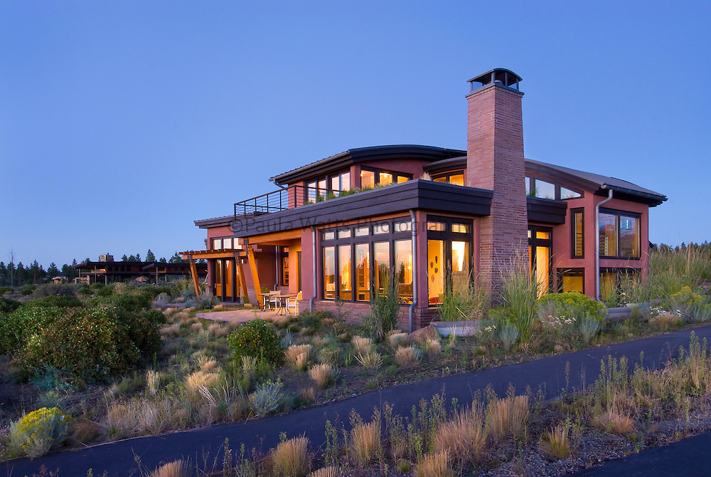 Modern barrel roofing design with spacious natural landscaping in mountain town