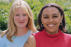 Portrait of two young women standing together outdoors smiling,
