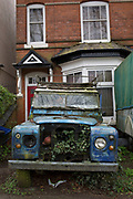 Dilapidated Land Rover parked on an overgrown drive in front of a house in Birmingham, England, United Kingdom.