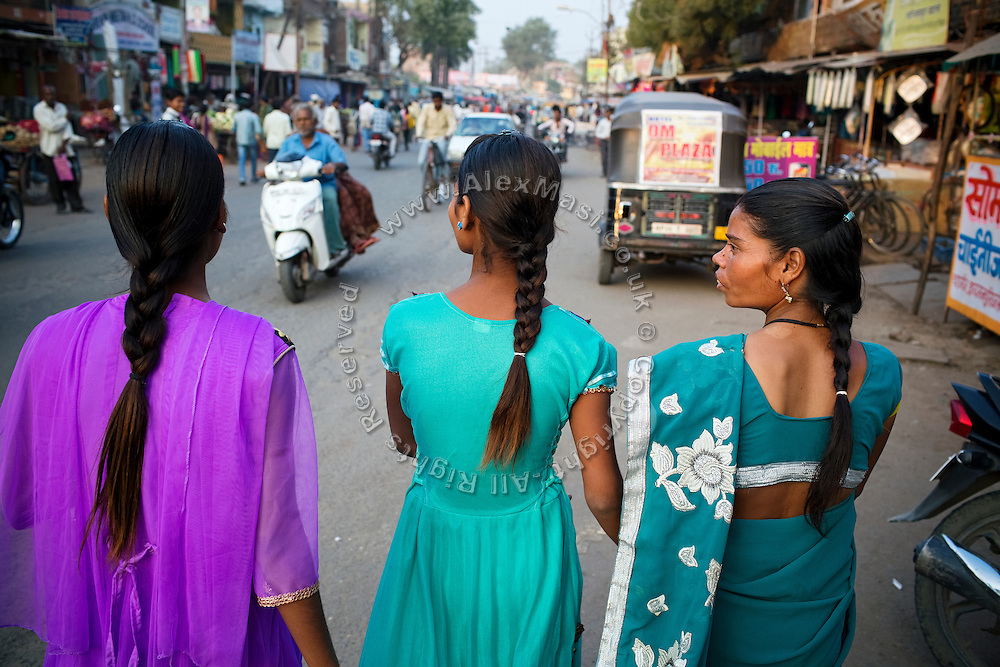 Poonam, 12, (centre) is walking with her mother Sangita, 41, (right) and her older sister Jyoti, 13, out shopping on a street close to their newly built home in Oriya Basti, one of the water-contaminated colonies of Bhopal, central India, near the abandoned Union Carbide (now DOW Chemical) industrial complex, site of the infamous '1984 Gas Disaster'.