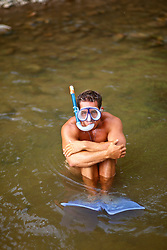 Man in a stream wearing snorkel mask, snorkel and fins
