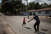 Ahmad Alsaloum, 4, runs into the arms of father Amin Alsaloum, 27, after chasing him down the street near their apartment in Tampa, Florida, U.S. Amin was headed to a market a few blocks away, and Ahmad wanted to join.