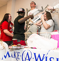 Lucy Tully, Justice Glover and Jordin Poire duct tape Craig Kozens Athletic Director/Dean of Students to the wall as Jag students raise money for the Make-A-Wish Foundation on Wednesday afternoon at Laconia High School.  (Karen Bobotas/for the Laconia Daily Sun)