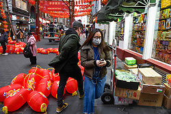 © Licensed to London News Pictures. 24/01/2020. LONDON, UK. A woman wears a facemask, possibly in reaction to the outbreak of the coronavirus in Wuhan, passing red lanterns to be hung in Chinatown ahead of Chinese New Year, the Year of the Rat.   Photo credit: Stephen Chung/LNP
