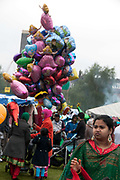Weavers Fields, Bethnal green, London. Boishakhi Mela, celebration for Bangladesh New Year. Asian woman and balloon seller
