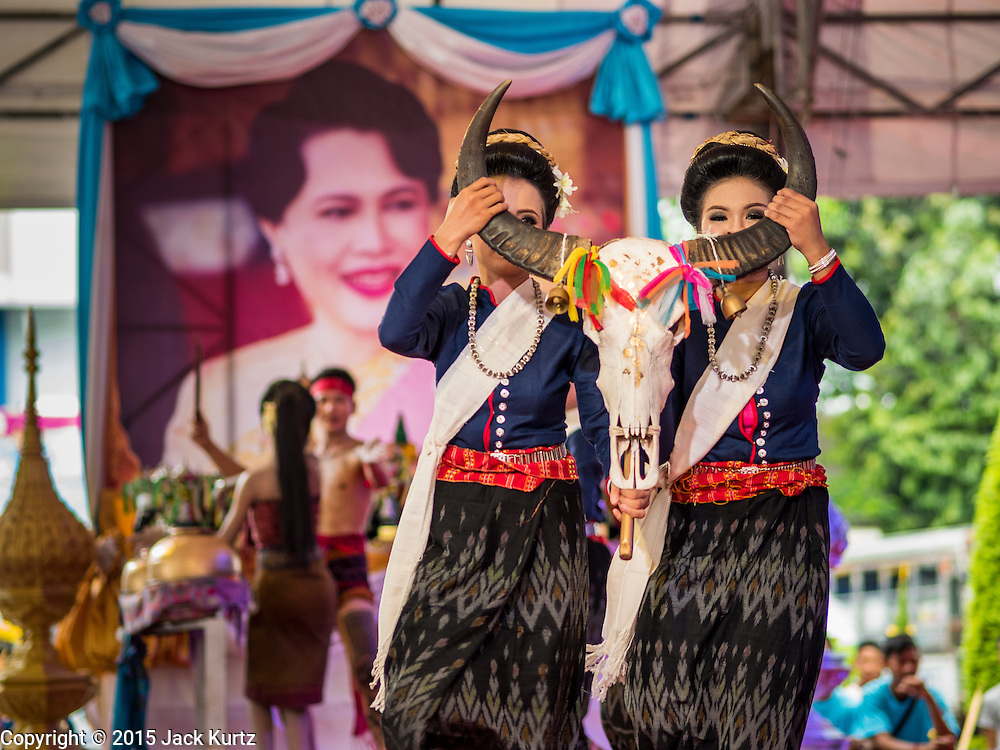 09 AUGUST 2015 - BANGKOK, THAILAND:  Women with a buffalo skull perform in front of a portrait of Queen Sirikit at a talent show to honor the Queen. Sirikit, born Mom Rajawongse Sirikit Kitiyakara on 12 August 1932, is the queen consort of Bhumibol Adulyadej, King (Rama IX) of Thailand. She met Bhumibol in Paris, where her father was the Thai ambassador. They married in 1950, shortly before Bhumibol's coronation. Sirikit was appointed Queen Regent in 1956. Sirikit produced one son and three daughters. As the consort of the king who is the world's longest-reigning head of state, she is also the world's longest-serving consort of a monarch. Sirikit suffered a stroke on 21 July 2012 and has since refrained from public appearances. Her birthday is celebrated as Mother's Day in Thailand.     PHOTO BY JACK KURTZ