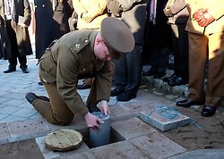 © Licensed to London News Pictures. <br /> 16/12/2014. <br /> <br /> Hartlepool, United Kingdom<br /> <br /> A member of the 18th Battalion The Durham Light Infantry Commemoration Society lowers a time capsule to be buried during an event to commemorate the bombardment of Hartlepool by German warships during World War One. During the bombardment 130 civilians were killed and more than 500 were wounded. The Headland's Heugh Gun Battery returned fire in what was the only battle to be fought on British soil during World War One, and one of the Battery's soldiers, Theo Jones of the Durham Light Infantry, became the first British soldier to be killed by enemy action on home ground in the war.<br /> <br /> Photo credit : Ian Forsyth/LNP