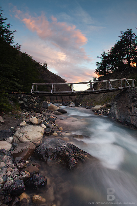Long exposure at sunset of a river and bridge at sunset in Valley Ascencio in Torres del Paine National Park in Patagonia, Chile.