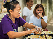 27 AUGUST 2016 - BANGKOK, THAILAND: A woman cooks traditional Thai dessert crepes during a lunch for residents of the Pom Mahakan slum. The Pom Mahakan community is known for fireworks, fighting cocks and bird cages. Mahakan Fort was built in 1783 during the reign of Siamese King Rama I. It was one of 14 fortresses designed to protect Bangkok from foreign invaders. Only two of the forts are still standing, the others have been torn down. A community developed in the fort when people started building houses and moving into it during the reign of King Rama V (1868-1910). The land was expropriated by Bangkok city government in 1992, but the people living in the fort refused to move. In 2004 courts ruled against the residents and said the city could evict them. The city vowed to start the evictions on Sept 3, 2016, but this week Thai Prime Minister Gen. Prayuth Chan-O-Cha, sided with the residents of the fort and said they should be allowed to stay. Residents are hopeful that the city will accede to the wishes of the Prime Minister and let them stay.       PHOTO BY JACK KURTZ