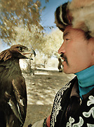 "A competitor and his master. The eagle is wearing its ""tomaga"", the hood that blinds her... and the basis of its domestication.<br /> <br /> Eagle Hunting festival in Western Mongolia, in the province of Bayan Olgii. Mongolian and Kazak eagle hunters come to compete for 2 days at this yearly gathering. Mongolia"