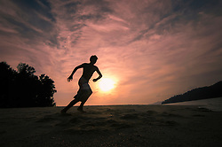 boy running at the beach at sunset, Koh Lipe, Thailand