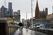 Locals are seen walking in the rain on Princess Bridge during COVID-19 in Melbourne, Australia. Victoria has recorded 14 COVID related deaths including a 20 year old, marking the youngest to die from Coronavirus in Australia, and an additional 372 new cases overnight. (Photo by Dave Hewison/Speed Media)