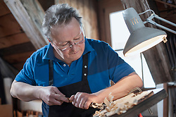 Craftsman carving violin