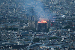 Smoke and flames rise during a fire at the landmark Notre-Dame Cathedral in central Paris on April 15, 2019, potentially involving renovation works being carried out at the site, the fire service said. Photo by Stephane Rochon Vollet/ABACAPRESS;COM