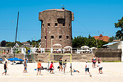 Young people playing ball games on St Aubin's sandy beach, Jersey, Channel Isles