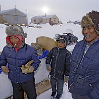 BAFFIN ISLAND, Nunavut, Canada. Inuit Guides prepare to load snowmobile sleds (kamatiks) in Clyde River.