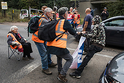 A man tries to pull away a banner from Insulate Britain climate activists blocking a slip road from the M25, causing a long tailback on the motorway, as part of a new campaign intended to push the UK government to make significant legislative change to start lowering emissions on 13th September 2021 in Godstone, United Kingdom. The activists, who wrote to Prime Minister Boris Johnson on 13th August, are demanding that the government immediately promises both to fully fund and ensure the insulation of all social housing in Britain by 2025 and to produce within four months a legally binding national plan to fully fund and ensure the full low-energy and low-carbon whole-house retrofit, with no externalised costs, of all homes in Britain by 2030 as part of a just transition to full decarbonisation of all parts of society and the economy.
